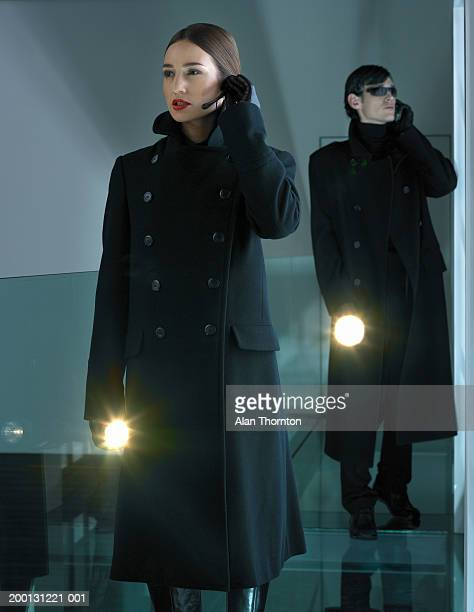 Man and woman using communication device, holding illuminated torches