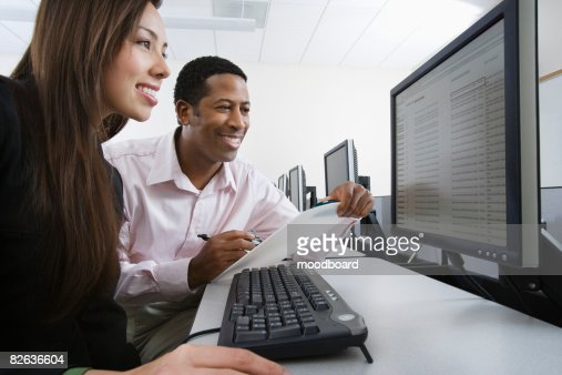 Man and woman using computer together : Stock-Foto