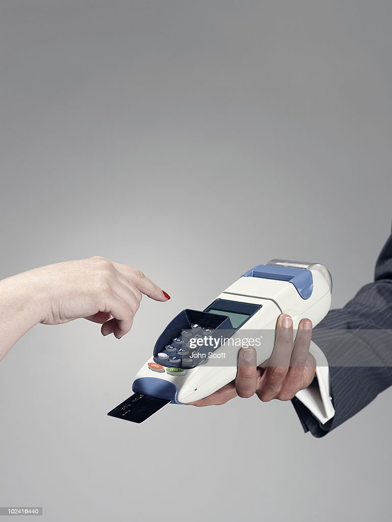 Man and woman using credit card terminal : Stock Photo