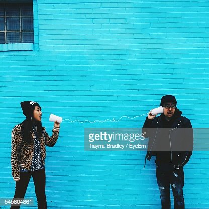 Man And Woman Using Cups And String To Communicate Against Blue Wall