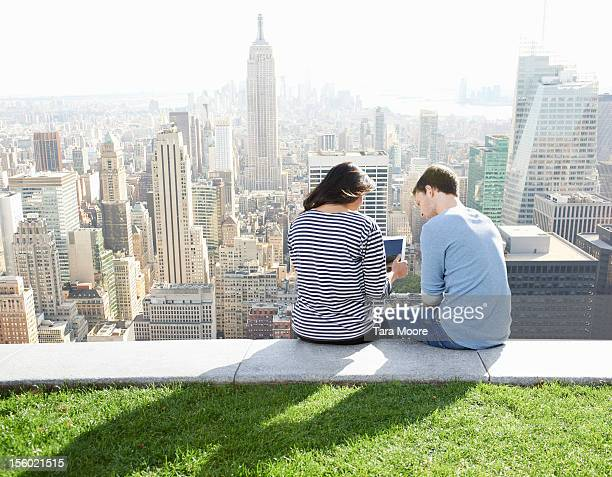 man and woman using digital tablet in city