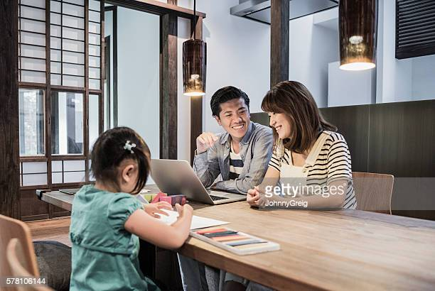 Man and woman using laptop, daughter drawing pictures