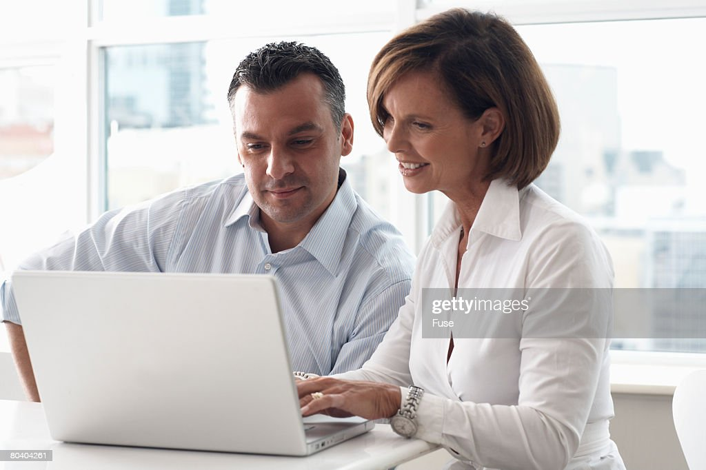 Man and Woman Using Laptop