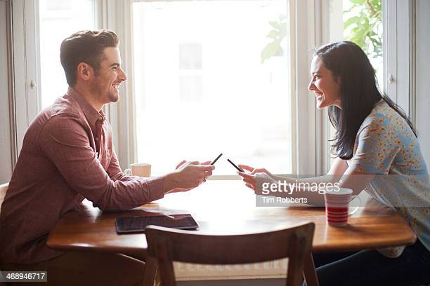Man and woman using smart phones at table.