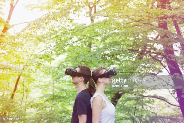 Man and woman using virtual reality headset in visionary forest
