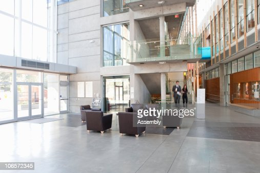man and woman walk down stairs to lobby of office  : Stock Photo