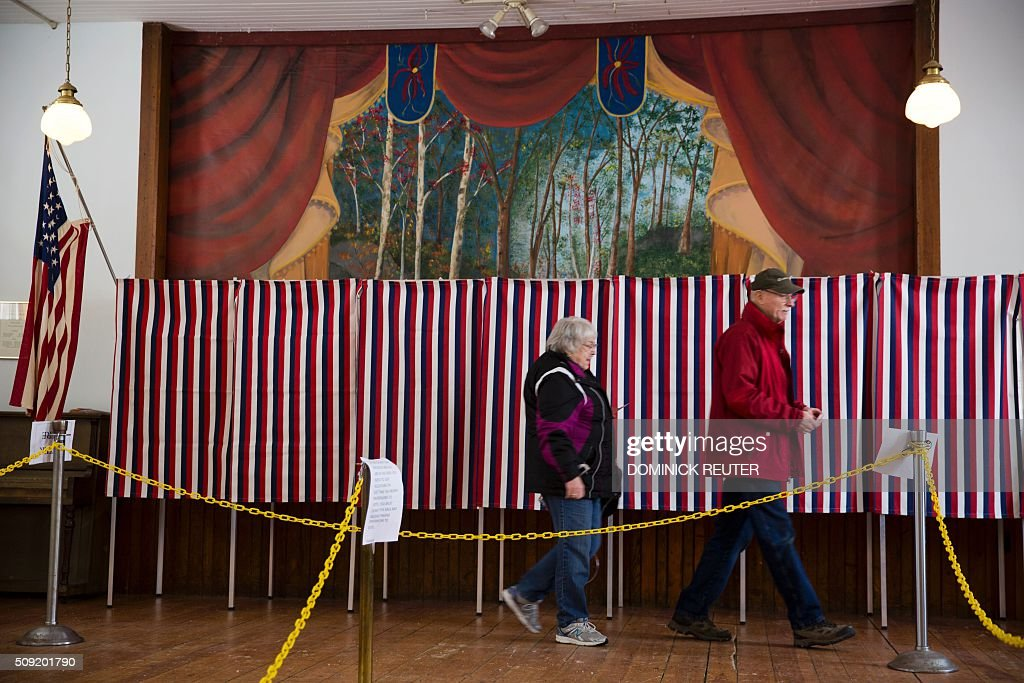 A man and woman walk past voting booths, February 9, 2016, in Chichester, New Hampshire. New Hampshire voters headed to polls at the snowy break of day Tuesday for the crucial first US presidential primary, with Donald Trump chasing victory and Hillary Clinton looking to narrow the gap on Bernie Sanders. / AFP / DOMINICK REUTER