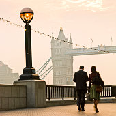 Man and woman walking by Tower Bridge