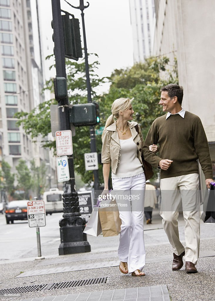 Man and woman walking down the street : Stock Photo