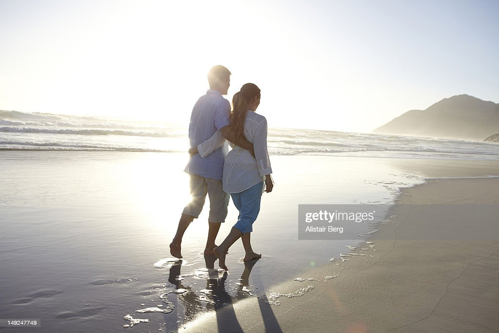 Man and woman walking on a beach together : Stock Photo