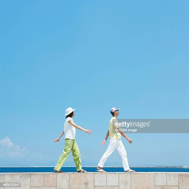 Man And Woman Walking On Breakwater