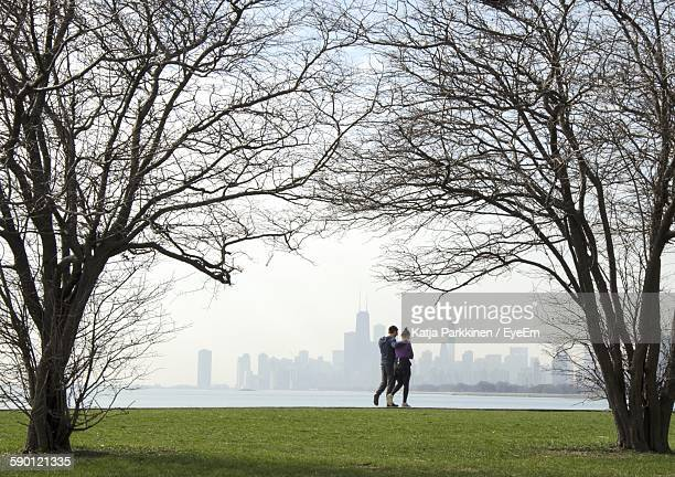 Man And Woman Walking On Field By Sea Against Cityscape
