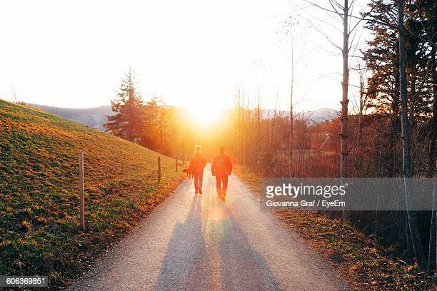 Man And Woman Walking On Street Against Sky During Sunset