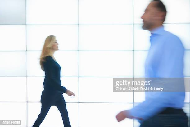 Man and woman walking past backlit wall panels