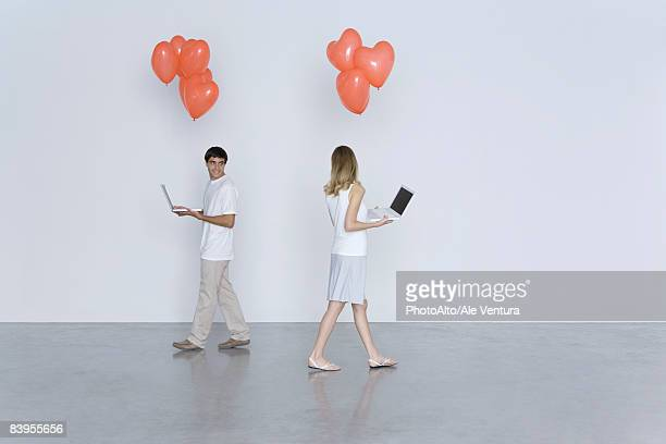 Man and woman walking past each other, both carrying laptop computers and heart balloons