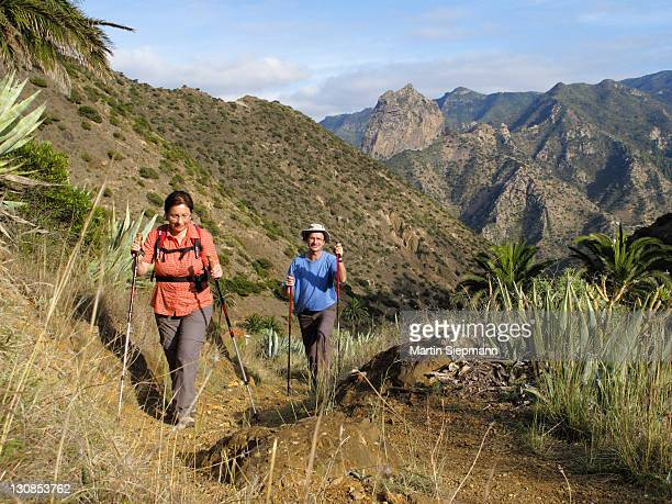 Man and woman walking with hiking poles in the Barranco de la Nueva Era, behind Roque Cano, Vallehermoso, La Gomera, Canary Islands, Spain, Europe