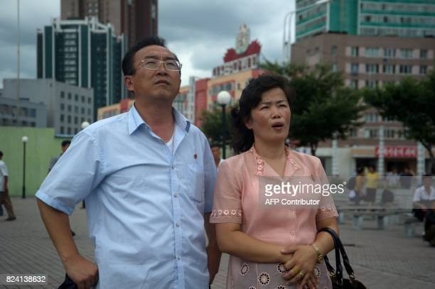 A man and woman watch coverage of an ICBM missile test displayed on a screen in a public square in Pyongyang on July 29 2017 Kim JongUn boasted of...