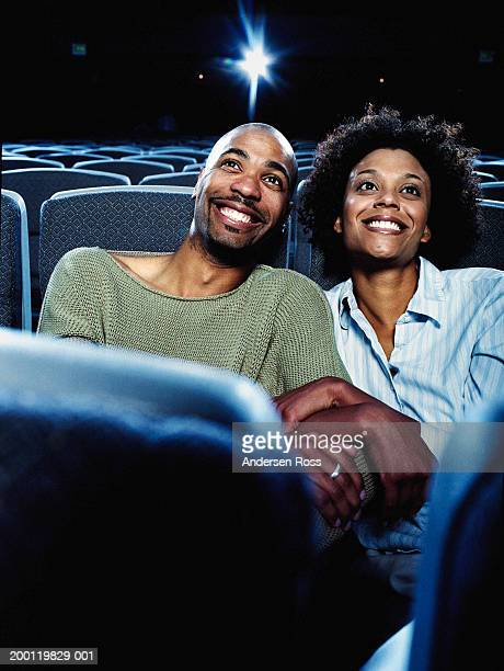 Man and woman watching movie in theater, smiling