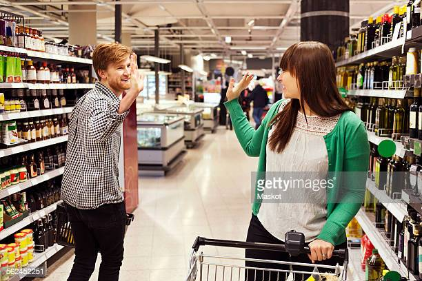 Man and woman waving at each other in supermarket