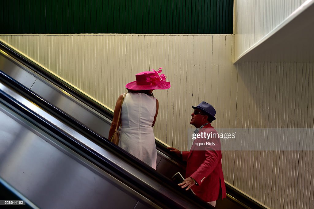 A man and woman wearing festive hats attend the 142nd running of the Kentucky Oaks at Churchill Downs on May 06, 2016 in Louisville, Kentucky.