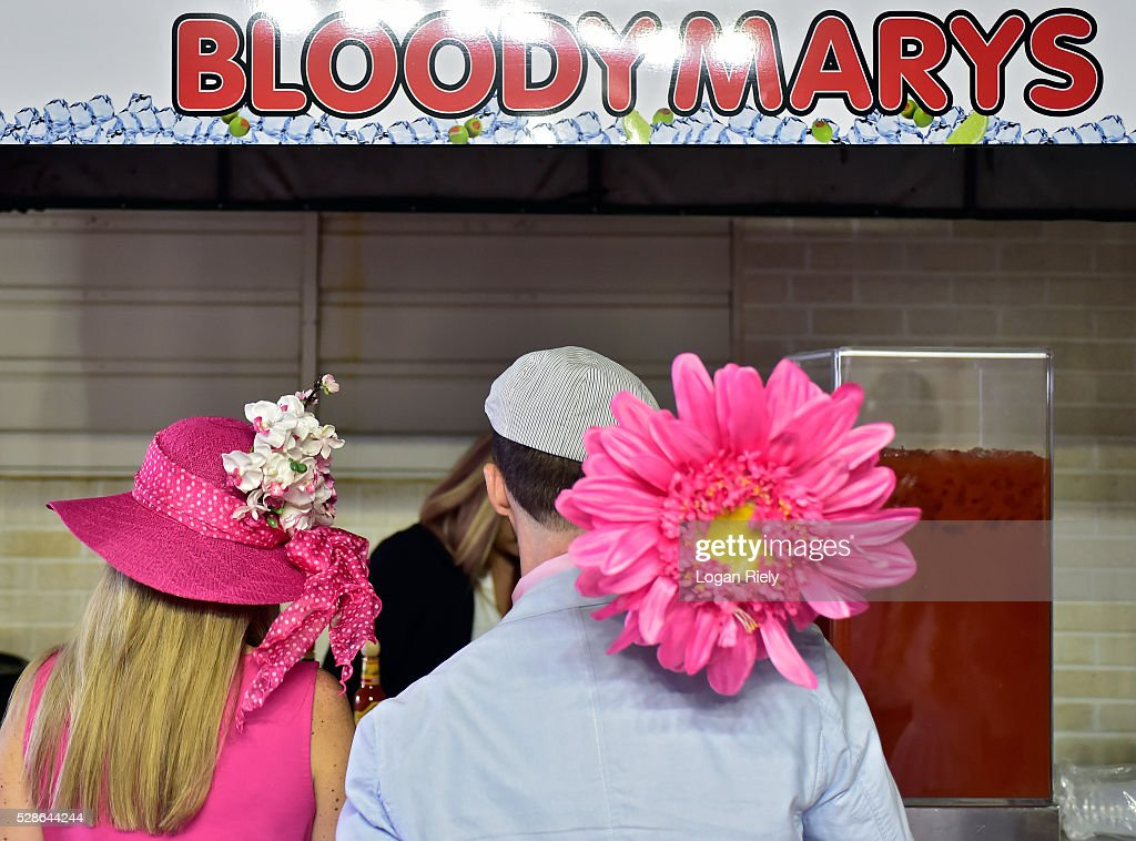 A man and woman wearing festive hats order Bloddy Marys drinks prior to the 142nd running of the Kentucky Oaks at Churchill Downs on May 06, 2016 in Louisville, Kentucky.