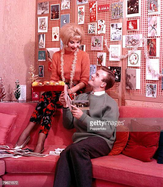 1960 A man and woman who are sitting on a sofa both wearing fashionable clothing whilst happily pinning up the Christmas decorations the woman also...