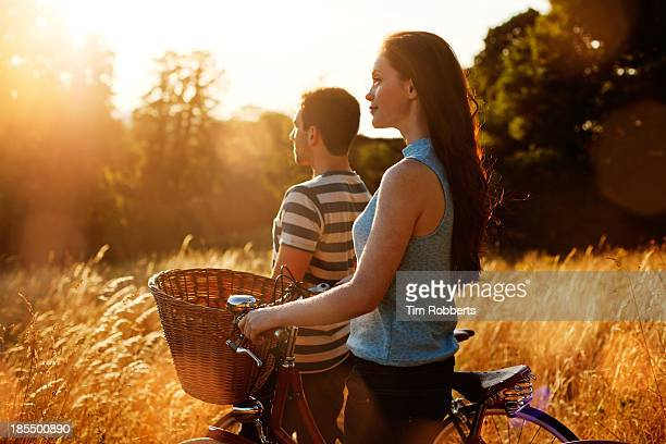 Man and woman with bikes in field at sunset.
