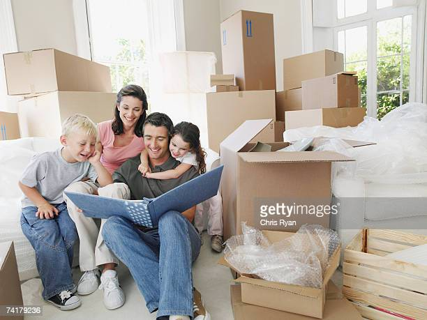 Mann und Frau mit Junge und Mädchen, die ein Foto-album