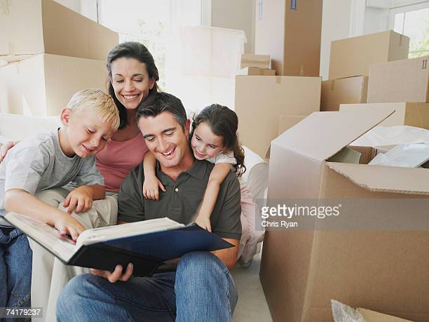 Man and woman with boy and girl looking at photo album in house with cardboard boxes