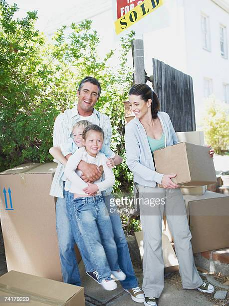 Man and woman with boy and girl outdoors with boxes and sold sign on house