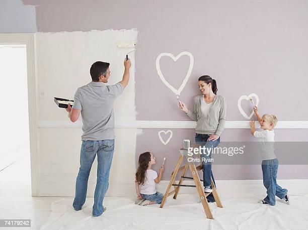 Homme et femme avec petit garçon et fille peindre coeur sur mur