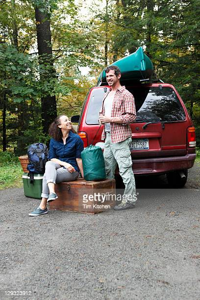 Man and woman with camping gear next to SUV