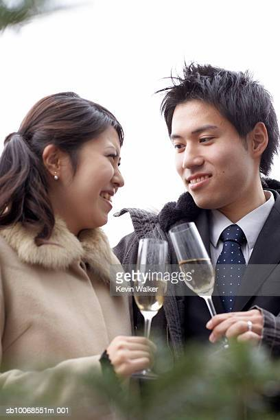 Man and woman with champagne flute talking at party