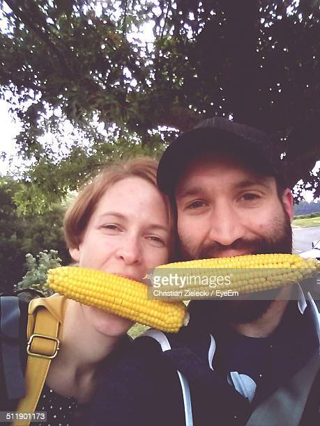 Man and woman with corn in mouth