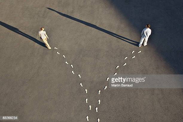Man and woman with diverging line of footprints