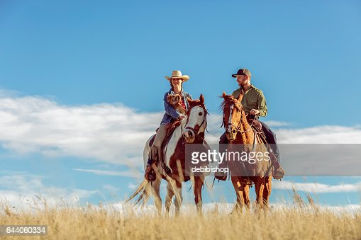 Man And Woman With Dog On Horseback Outdoors Grassy Prairie