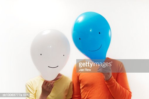Man and woman with faces obscured by faced balloons : Stock Photo