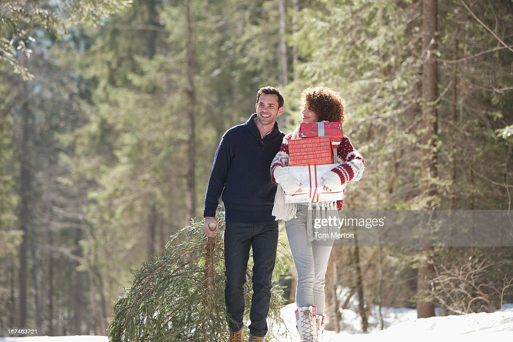 Man and woman with gifts outdoors, winter : Stock Photo