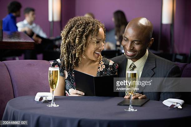 Man and woman with glasses of champagne looking at menu in restaurant