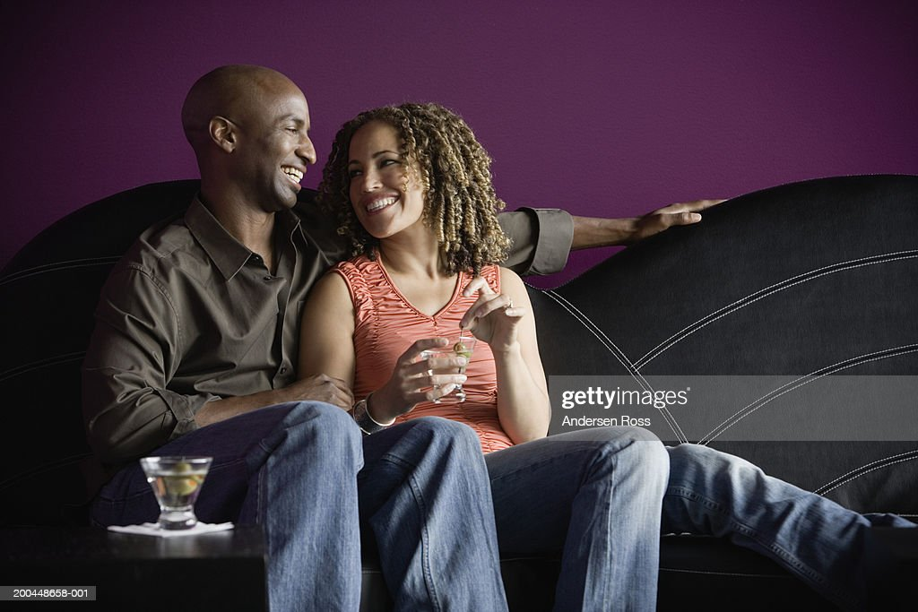 Man and woman with martinis sitting on sofa, smiling at one another : Stock Photo