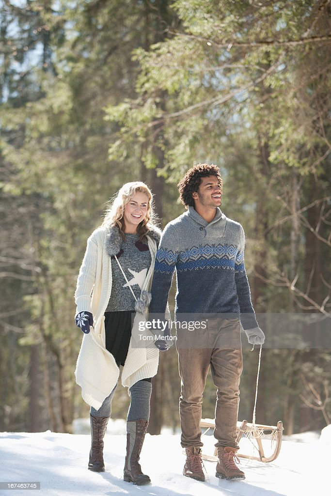 Man and woman with sled in snowy landscape : Stock Photo