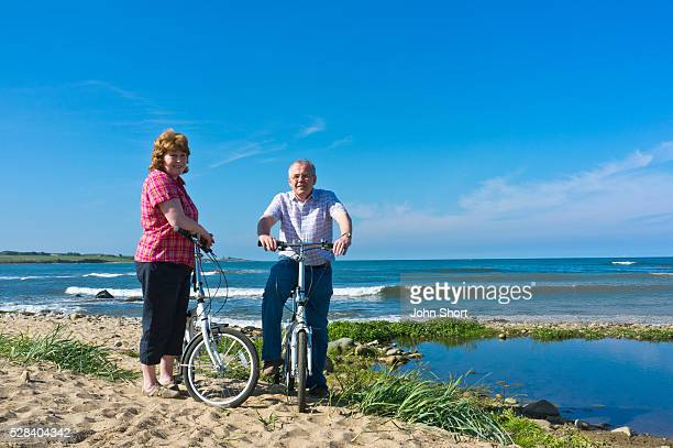 A Man And Woman With Their Bicycles On The Beach; Northumberland England