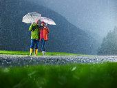 Hombre y mujer con paraguas jugando en la lluvia.