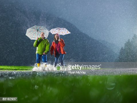 Mann und Frau mit Sonnenschirmen Spielen im Regen. : Stock-Foto