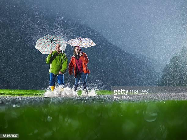 Homme et Femme jouant avec des parapluies sous la pluie.