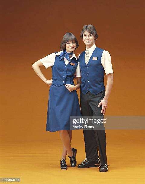 Man and woman with uniform standing against orange background