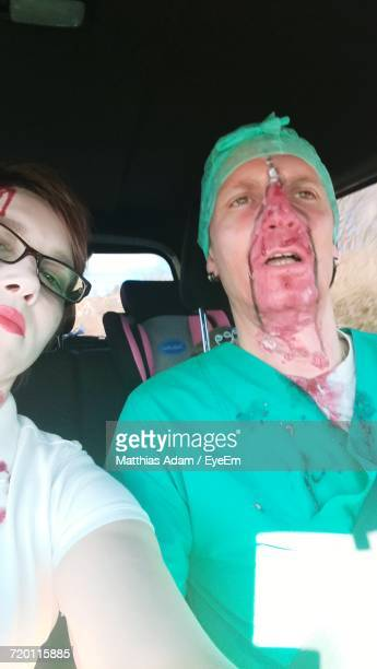 Man And Woman With Zombie Make-Up Sitting In Car