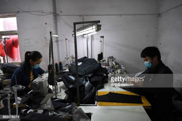 A man and woman work in a clothing factory on the outskirts of Beijing on October 20 2017 China's economy slowed marginally in the third quarter but...
