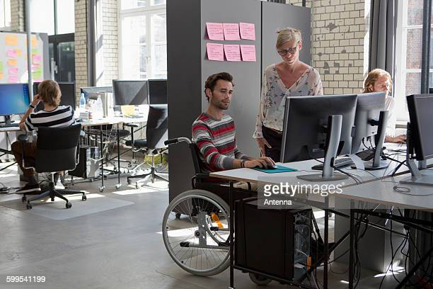 Man and woman working on computer in office
