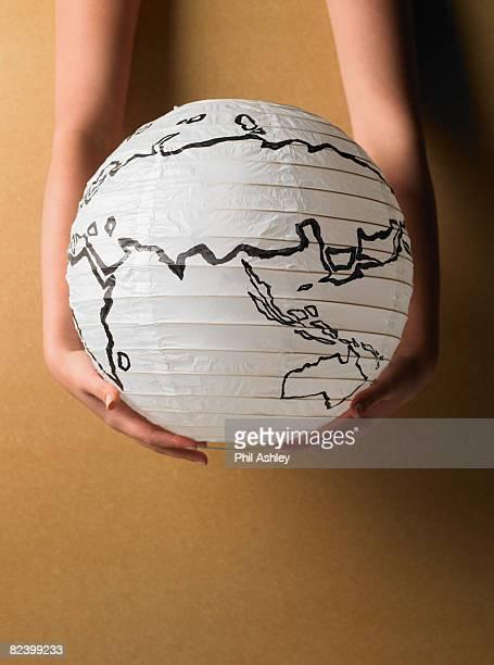 Mann und Frau Hände halten einen Globus Lampe